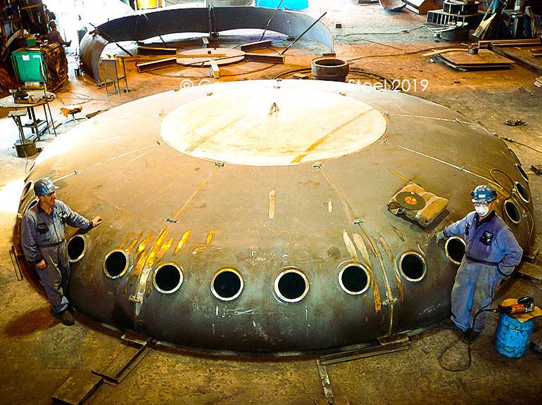 Flued holes being cut on a multi segmented tank head